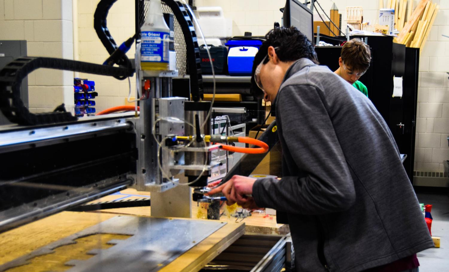 High-powered machinery: robotics team member Jonah Rosenthal adjusts the router.
